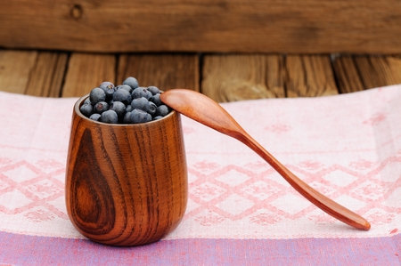 Handmade wooden vase full with fresh wild blueberries with wooden spoon on pink cotton cloth horizontal