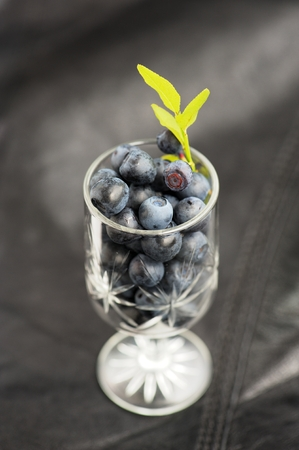 Wild blueberries with fresh green leaves in small wineglass on black leather background vertical