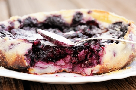 French pie clafoutis with cherry and spoon in white plate closeup macro Zdjęcie Seryjne