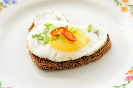 Fried egg heart rye sandwich with scallion and chili on white plate horizontal