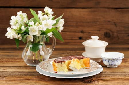 Homemade baked pudding with chololate icing, jasmine flowers in glass jar and chinese teaware on wooden background copyspace horizontal