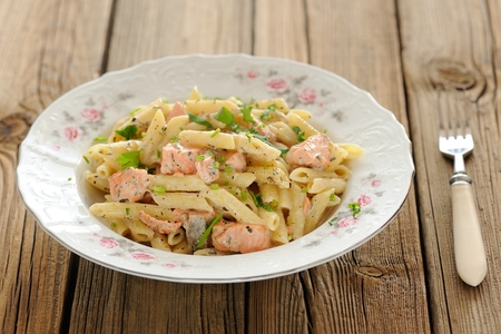Creamy pasta with salmon and parsley in white plate horizontal