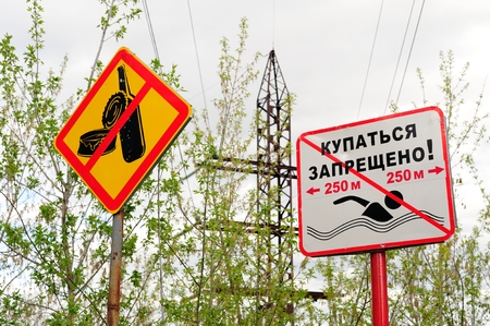 Signs Do not bathe and Do not litter, electric power transmission on background horizontal