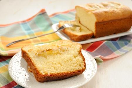 Mascarpone cake slice, long fork on white bright background horizontal