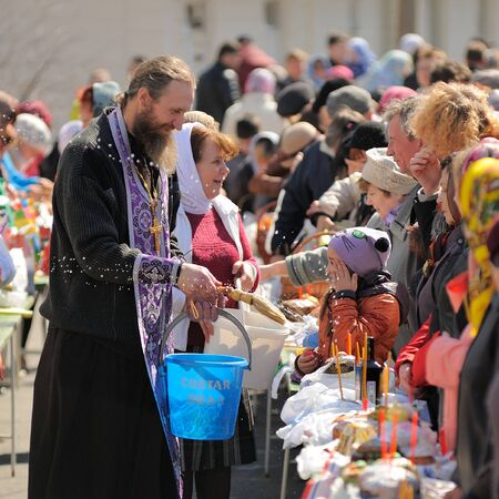 Orel, Russia, April 11, 2015: Traditional orthodox paschal ritual - priest blessing easter eggs and kulitches with holy water in blue bascket