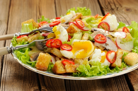 Salad Caesar with mushrooms, eggs, chili and radish with two forks on wooden background horizontal