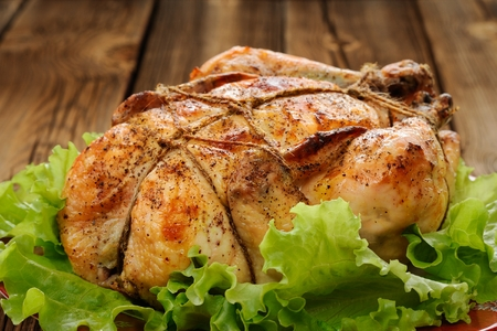 Bondage shibari roasted chicken with salad leaves on red plate on wooden background closeup horizontal