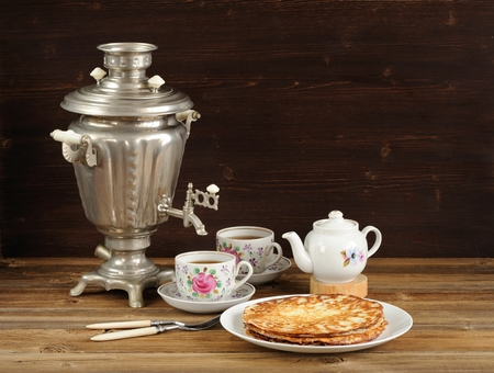 Russian bliny with vintage samovar and teaware horizontal space background