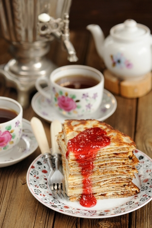 Russian bliny with raspberry jam, vintage samovar and teaware vertical selective focus Standard-Bild