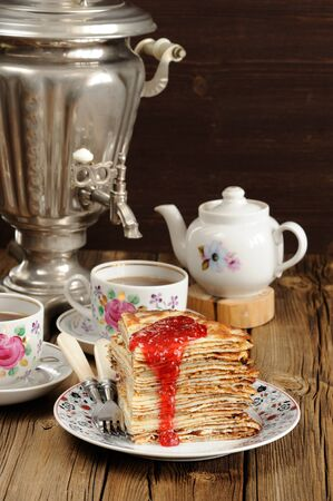 Russian bliny with raspberry jam, vintage samovar and teaware vertical Stock Photo