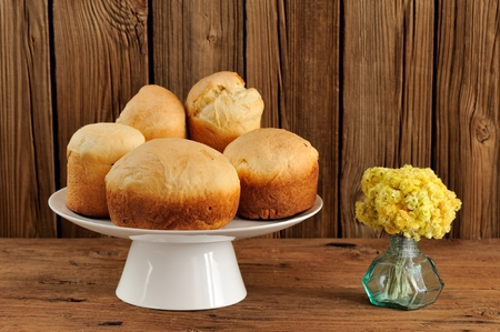 Paska, East European easter sweet breads on white pedestal with yellow flowers on wooden background horizontal with space Stock Photo