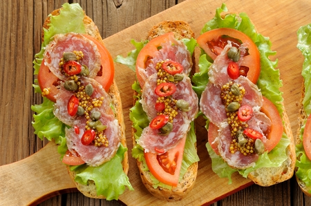 Sandwiches with ham, salad leaves, chili, tomatoes, capers, french mustard on wooden background horizontal