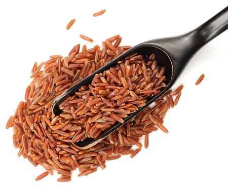 Red raw rice in black wooden spoon, isolated Foto de archivo