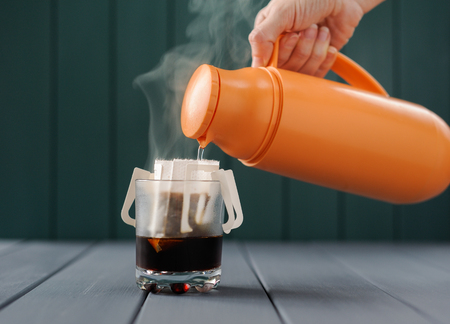 Making drip coffee with hot water from thermos front view