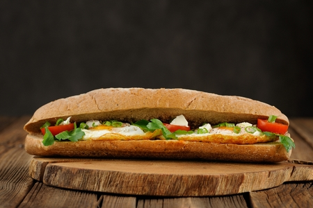 Rye bread egg sandwich with tomatoes and greens with gray space background