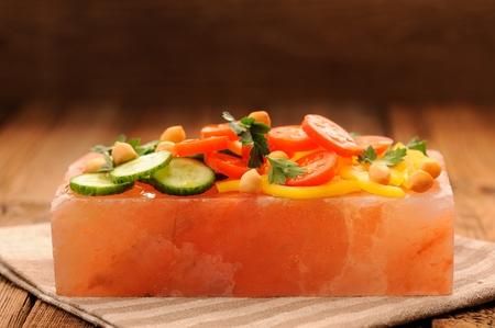 Vegetable salad on pink salt block on stripe napkin and wooden background