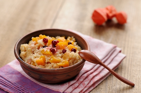 Millet porrige with pumpkin in clay bowl with wooden spoon on wooden background