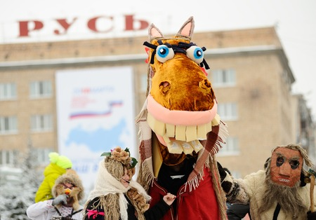 Orel, Russia, February 18, 2018: Maslenitsa carnival. People in scary masks at Rus sigh background