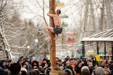 Orel, Russia, February 18, 2018: Maslenitsa carnival. Naked man climbing pole and crowd of people watching him