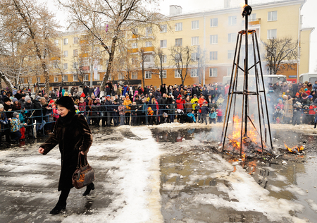 Orel, Russia, February 18, 2018: Maslenitsa carnival. People watch burnt Lady Maslenitsa and lady in fur going out Editorial