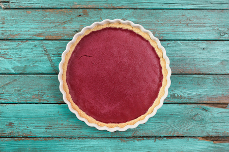 Minimalist dessert. Round lingonberry pie on shabby wooden blue background copyspace top view Stock Photo