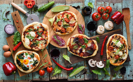Flatlay of healthy domestic food Italian style. Rustic pizzas with vegetables, salami, eggs and mushrooms served with red wine on oak chopping boards over shabby blue background overhead view Stock Photo