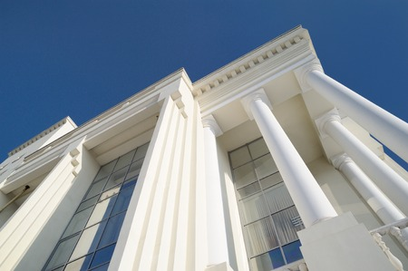 Classic style white building facade detail with pillars against clear blue sky. Modern architecture. Low angle view