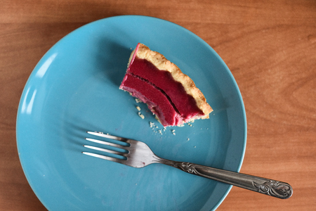 Homemade tasty berry pie half eaten on blue plate top view