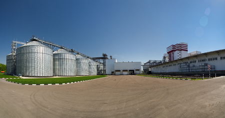 Modern animal feed factory. Panoramic view of new granaries, big metal containers for grain and empty square