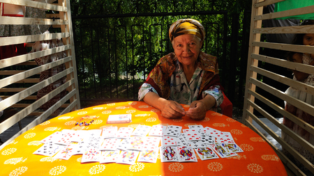 Orel, Russia - August 04, 2018: Samovar fest. Senior fortuneteller with cards looking at your eyes
