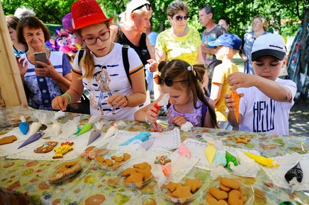 Orel, Russia - August 04, 2018: Samovar fest. Children paint homemade cookies with food coloring closeup