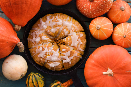Heritage baking. Traditional triangular pumpkin scones in cast iron pan with raw pumpkins on blue background top view