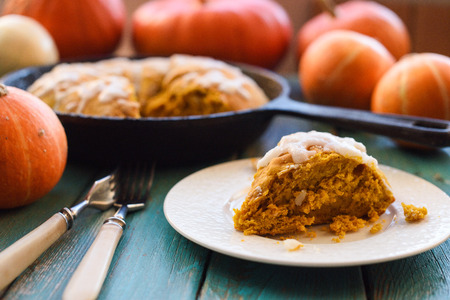 Heritage baking. Pumpkin scones in cast iron pan with sugar icing served with pumpkins on blue background closeup