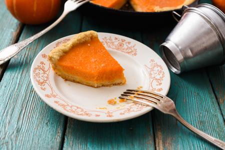 Homemade pumpkin dessert. Piece of traditional open pumpkin pie being eaten closeup