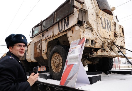 Orel, Russia, February 25, 2019: Syrian Break - trophy exhibition train of Russian Defence Ministry. Serviceman in uniform taking photo of armored Syrian vehicle on platform