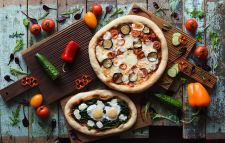 Homemade rustic style big puffy pizza with aubergines, tomatoes and bell peppers served with raw ingredients on oak boards on shabby blue background top view copyspace