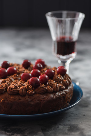 Healthy low sugar homemade chocolate cake with chocolate icing and raw cherries served with red wine on dark concrete background copyspace