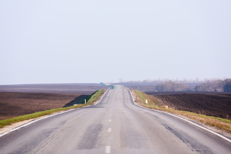 Serene countryside lanscape. Empty asphalt road in empty fields and clear sky in sunny day copyspace. Traveling lonely concept Stock Photo