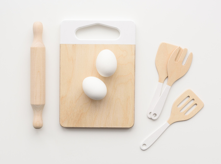 Wooden toys for children. Play kitchen utensils: cutting board, rolling pin and spatulas with raw eggs on white background top view