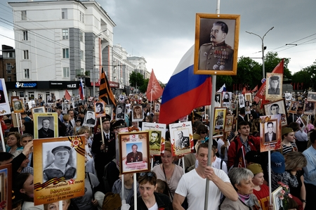 Orel, Russia, May 09, 2019: Victory Day, Immortal Regiment parade. Huge crowd of people marching with flags, portraits of soldiers and Stalin on pole