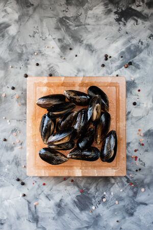 Salt block cooking. Mussels in shells roasted on square pink Himalayan salt block on concrete background top view copy space