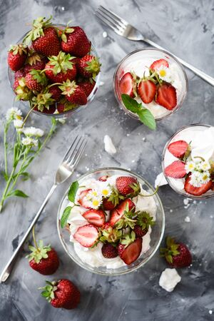 Flatlay of healthy strawberry dessert. Eton mess with whipped cream and berries top view