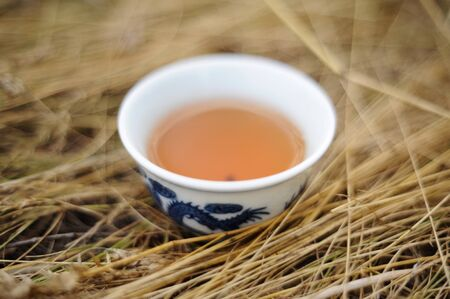 Healthy beverage. Black tea in Chinese bowl in dry grass closeup