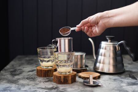 Making pour over coffee with condensed milk Vietnamese style. Woman hand pouring ground coffee into phin on dark background copy space
