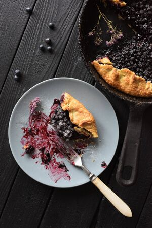 Healthy homemade pastry. Delicious crusty blueberry galette being eaten on black background top view