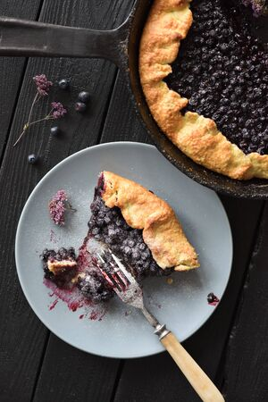 Homemade delicious blueberry pie being eaten on black background top view