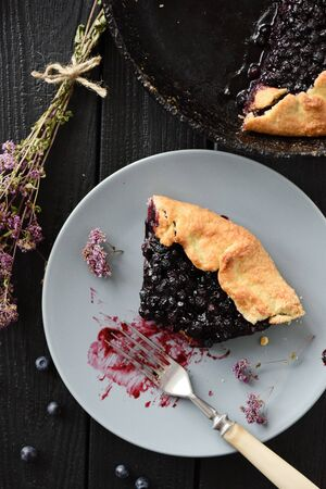 Piece of homemade blueberry galette being eaten on black background rustic style top view