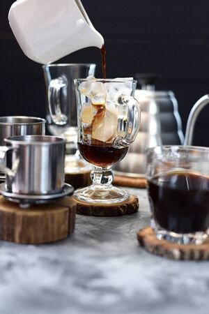 Making Vietnamese ice coffee. Pouring black coffee into glass with ice cubes on dark background copy space