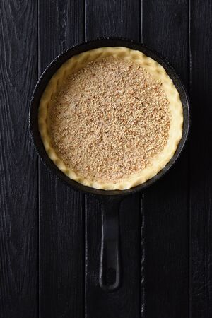 Shortcrust pastry. Raw crust with chopped almonds for open pie in cast iron pan on black background top view copy space overhead view Banco de Imagens