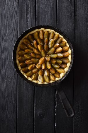 Raw homemade flower shape plum pie in cast iron pan on black background top view minimalist style. Low key still life with natural lighting copy space overhead view Banco de Imagens